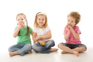 three children eating apple